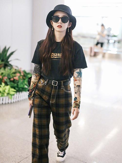 Mạnh Mỹ Kỳ diện thêm áo họa tiết bên trong áo phông đen, tăng độ cá tính.