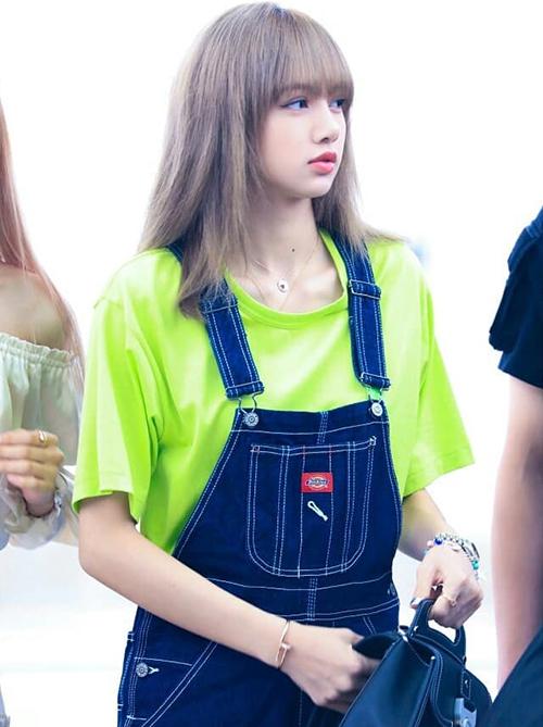 Lisa cũng gây chú ý khi mix-match áo phông xanh dạ quang, quần yếm jeans