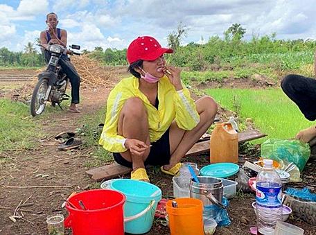 Cô ngồi ăn cơm với cá khô cùng bà con.