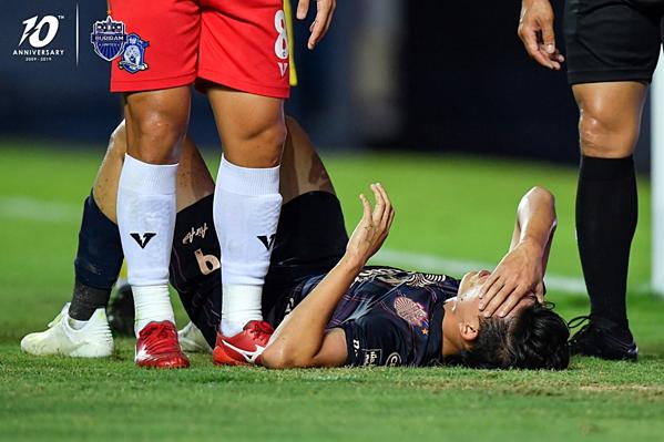 Supachai Jaided nằm sân đau đớn sau pha va chạm với cầu thủ đối phương.