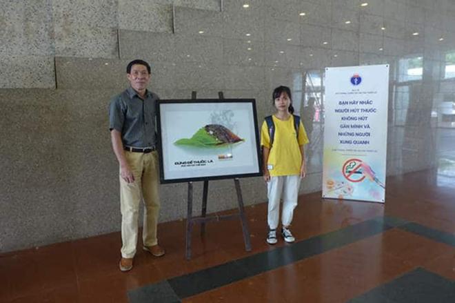 Nguyễn Thị Hồng Vân (áo vàng) chụp ảnh cùng tác phẩm của mình.