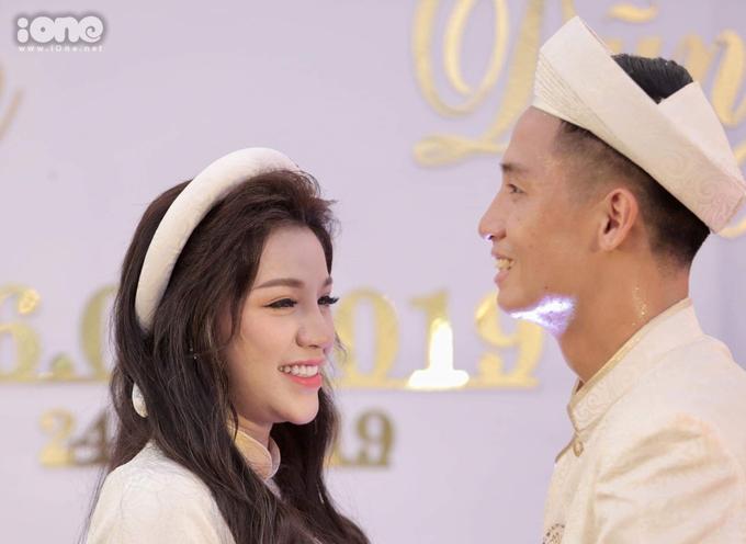 """<p> Cô dâu Khánh Linh mỉm cười e thẹn khi chồng sắp cưới """"đòi"""" hôn. Theo lời gợi ý của MC đám hỏi, chú rể hoặc là hát hoặc hôn cô dâu. Tiến Dũng """"láu cá"""" chọn cả hai. <em>Ảnh: Hiếu Lương.</em></p>"""