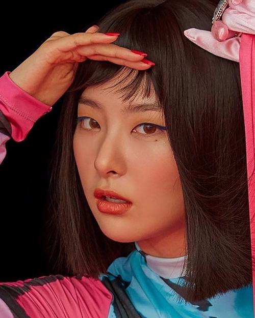 Gây chú ý với lối trang điểm cá tính, sắc sảo không ai khác ngoài Seul Gi. Cô nàng chọn phấn mắt màu bơ đậu phộng Peanut Butter giá 300k của VDL và nhấn nhá thêm đường kẻ mắt màu xanh nổi bật Aquamatic I-22 Iridescent Blue gần 814k của Make Up For Ever. Thay vì chọn màu má đơn sắc như đồng đội thì Seul Gi lại phá cách khi phối 2 màu là hồng nhạt Mono Pink, hồng nude Nude Peach của 3CE 395k với màu son Lip Motion Lipstick MBR02 360k.