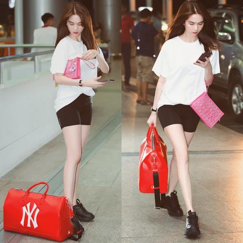 Ngọc Trinh mặc áo thun trắng cùng biker shorts đen đơn giản ra sân bay. Cô nàng tạo điểm nhấn bằng túi xách đỏ.