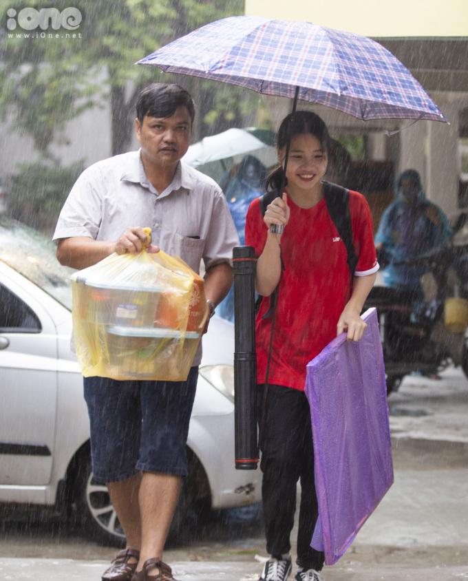 <p> Nữ sinh này cùng người thân lỉnh kỉnh đồ đạc bước đi giữa cơn mưa nặng hạt.</p>