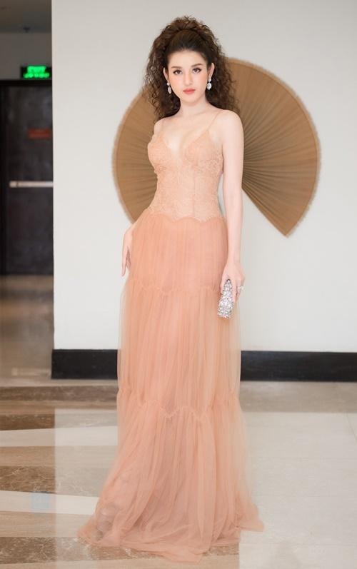 Á hậu sinh năm 1995trung thành với phong cách gợi cảm. Cô diện đầm hai dây, chất liệu ren xuyên thấu gam màu nude, khoe vòng một đẫy đà.