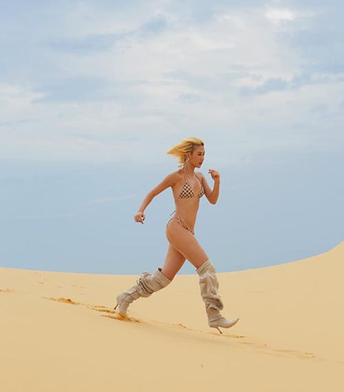 Bức ảnh mới của Quỳnh Anh Shyn đang làm rộ lên tranh cãi. Giữa sa mạc cát, hot girl sải bước chạy với bộ bikini nhỏ xíu và đôi boots cao gót lùng bùng.