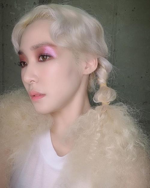 Tiffany chơi trội với lớp phấn mắt đậm, dày. Mái tóc của cô nàng được nhuộm màu vàng kim bông xù như tóc búp bê Barbie.