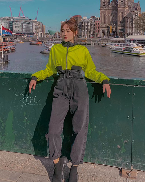 Dạo phố châu Âu, Minh Hằng mặc áo khoác neon cùng quần jeans ống rộng chất lừ.