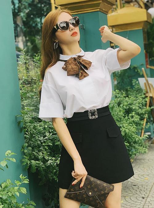 Hạnh Sino diện sơ mi trắng váy đen theo kiểu nữ sinh, tuy nhiên kết hợp cả bộ phụ kiện Louis Vuitton tăng đẳng cấp.