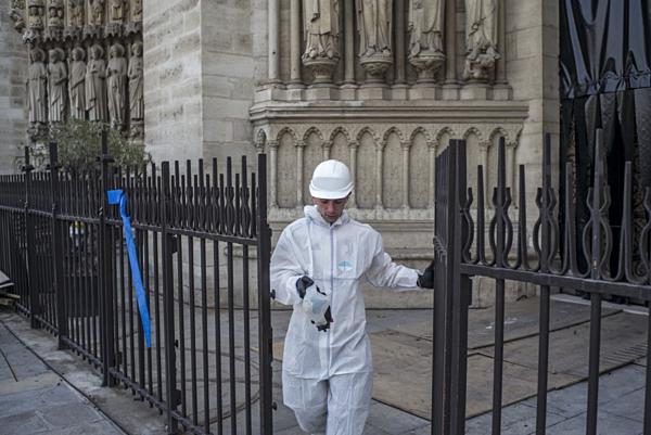 Công nhân xây dựng đi qua cổng Nhà thờ Đức Bà trong ngày phục dựng tòa nhà. Ảnh: AFP