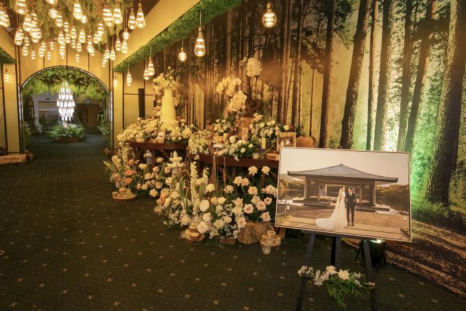 <p> Sảnh ngoài được trang trí nhiều hoa và đèn. Ảnh cưới lớn cũng được đặt ở khu vực này.</p>