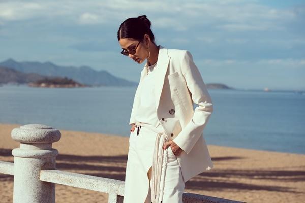 Bộ trang phục tông trắng của NTK Lâm Gia Khang được Hoàng Thùy diện ở bãi biển.