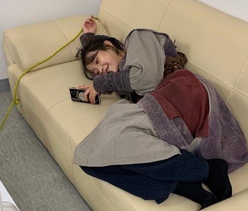 IU mặc nguyên phục trang vừa nằm xem điện thoại vừa cười một mình.