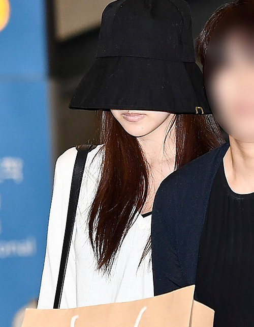 Mina đội mũ che kín mặt khi hạ cánh xuống Seoul.