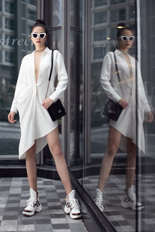 Áo sơ mi dáng dài xẻ sâu tận rốn khai thác tối đa vẻ gợi cảm của Hoàng Hạnh. Cô mix mẫu áo sexy cùng sneakers của Louis Vuitton, túi Chanel và kính mắt Miu Miu.