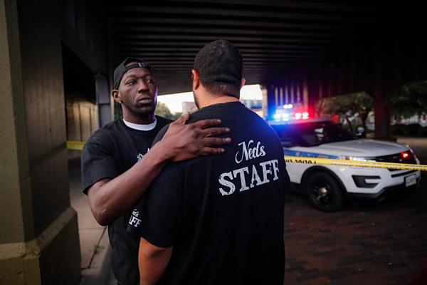 Các nhân chứng an ủi nhau tại hiện trường vụ xả súng hàng loạt ở Dayton, Ohio. Ảnh: John Minchillo/ AP.
