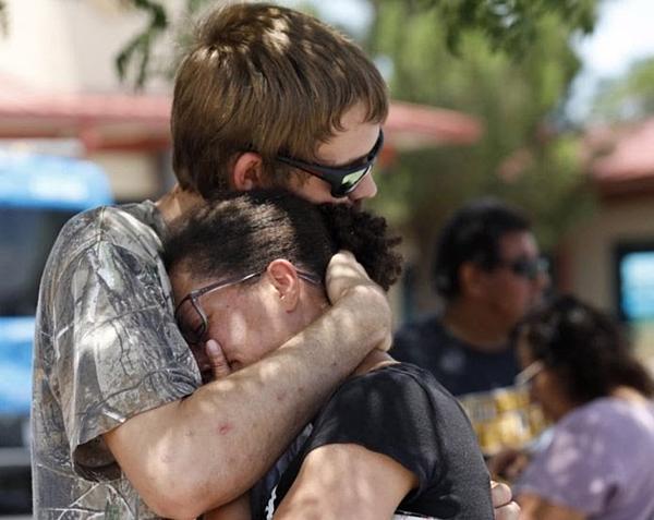 Nạn nhân ôm nhau khóctrong vụ xả súng siêu thị Walmart ở bang Texas, Mỹ, ngày 3/8. Ảnh: AP.