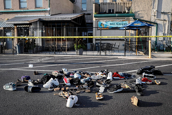 Shoes are piled outside the scene of a mass shooting near Ned Peppers Bar Aug. 4, 2019, in Dayton, Ohio. AP Photo/John Minchillo