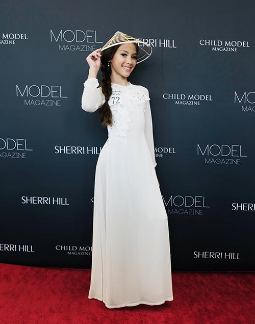 Trong buổi trình diễn trang phục tự chọn tại thảm đỏ, Lucy chọn Áo Dài lụa trắng của Nhà thiết kế Phương Nguyễn Silk - chuyên áo dài trẻ em tại Việt Nam, kết hợp nón khung bỏ lá.