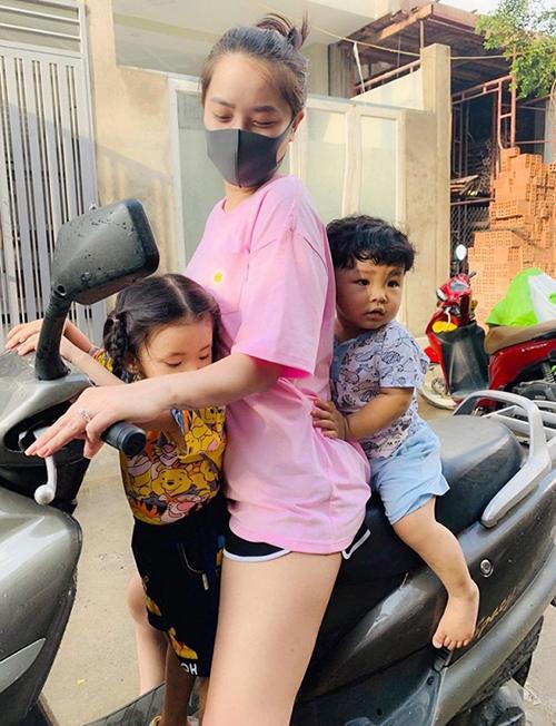 Hải Băng chở hai con đi chợ bằng xe máy.