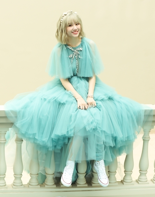 Bộ váy màu xanh ngọc với chất liệu lụa Italian với các chi tiết xếp ly cầu kỳ ở phần thân và hai bên cầu vai. Thay vì lựa chọn kết hợp với giày cao gót, Hari quyết định chọn giày thể thao từ thương hiệu Converse.