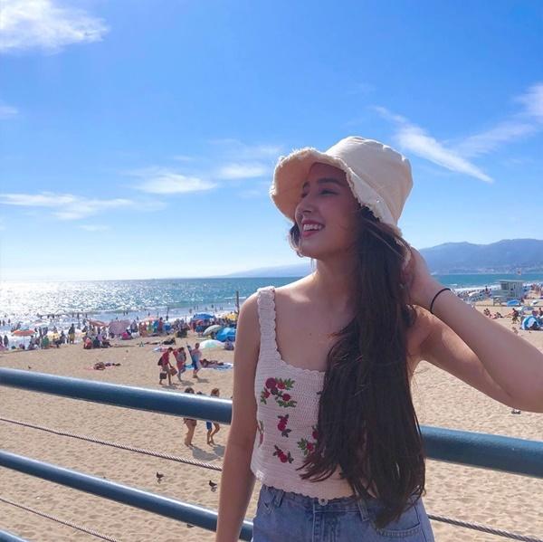 Nancy rạng rỡ đi biển với áo hai dây và mũ vải.