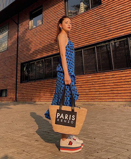 Chi Pu chọn mẫu túi tote chất liệu cói của Kenzo, rất phù hợp với thời trang mát mẻ mùa hè.