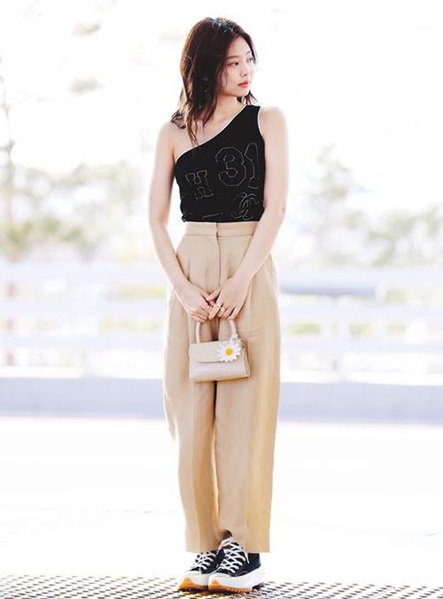 Khi mặc quần ống rộng và giày thể thao, Jennie thêm nét nữ tính vào trang phục bằng chiếc áo lệch vai đi kèm túi xách đính hoa xinh xắn.