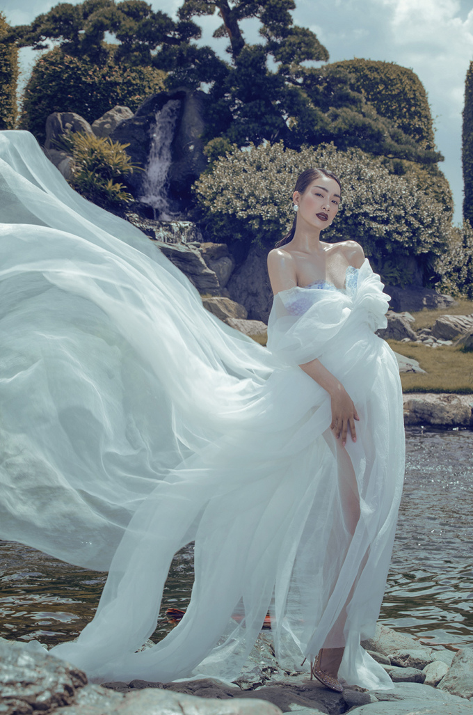 """<p> Nhà thiết kế Hoàng Minh Hà chọn Coco Thùy Dung làm """"nàng thơ"""" vì vẻ đẹp khỏe khoắn. Thiết kế với chất liệu vải suôn mềm mại với hai tone trắng - xanh chủ đạo, xẻ sâu giúp cô khoe vẻ gợi cảm.</p>"""