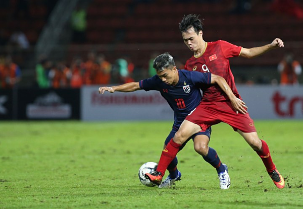 Văn Toàn (áo đỏ) trong một pha đối đầu với tiền vệ ngôi sao của Thái Lan, Chanathip.