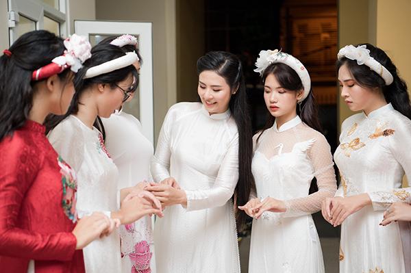 Ở hậu trường của buổi lễ, Hoa hậu Việt Nam 2010 tất bật giúp các em nữ sinh chuẩn bị cho màn trình diễn áo dài. Cô tự tay chỉnh sửa từng chi tiết về trang phục, thậm chí giúp các model không chuyên tạo kiểu tóc.