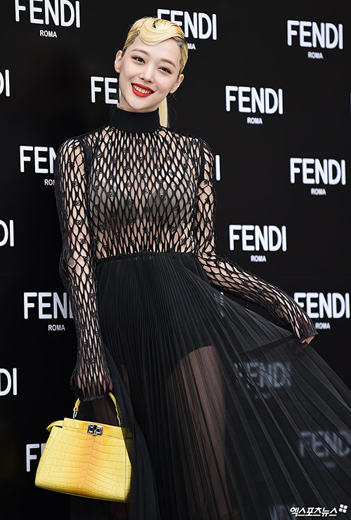 Sulli trong sự kiện mới đây cũng làm dân tình rạo rực khi lên đồ xuyên thấu gợi cảm và cầm trên tay chiếc túi màu vàng nổi bật Peekaboo Mini Crocodile Bag của nhà mốt Fendi giá 23.000 USD, xấp xỉ 535 triệu đồng.