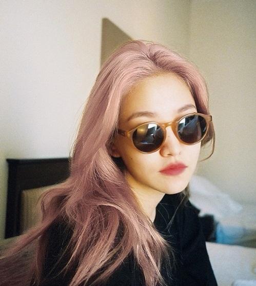 Yeri đeo kính đen sành điệu với mái tóc hồng chất chơi.