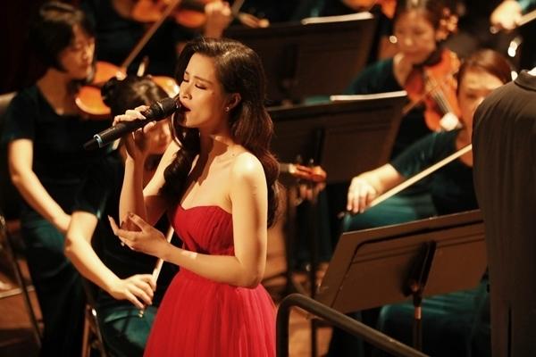 Đông Nhi diện chiếc đầm đỏ công chúa. Nữ ca sĩ mở đầu bằng ca khúc Xin anh đừng.