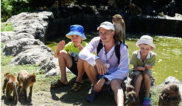 Khách du lịch tạo dáng với khỉ tại Đảo Khỉ. Ảnh: Khắc Nguyễn / AFP.