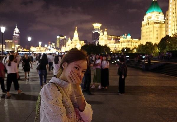 Hyo Min ngại ngùng che mặt khi dạo chơi ở Thượng Hải mà không bịt khẩu trang.