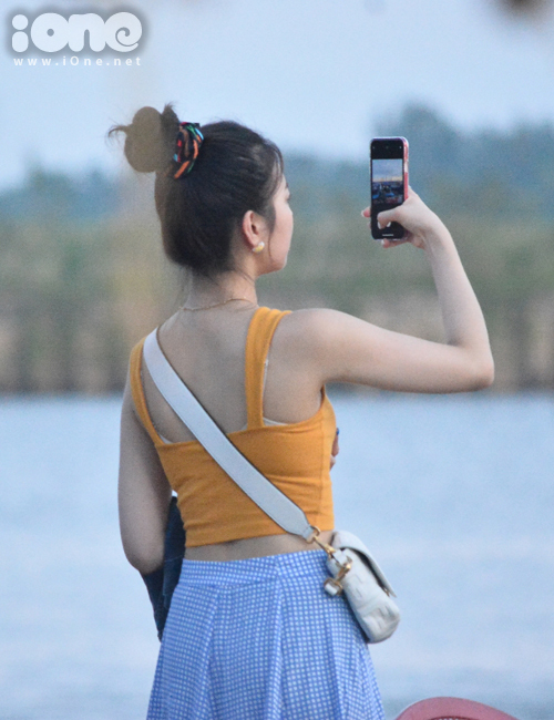Trong trang phục đời thường mát mẻ và khỏe khoắn, nữ ca sĩ đi dạo phố, mua sắm đồ lưu niệm ở chợ đêm Nguyễn Hoàng, liên tục chụp lại cảnh đẹp bằng điện thoại.