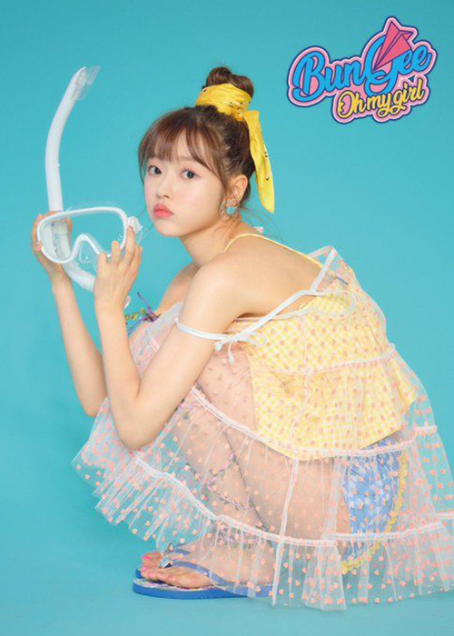 Cô nàng búp bê YooA (Oh my girl) kết hợp tóc bối cao với chiếc khăn vàng làm điểm nhấn.