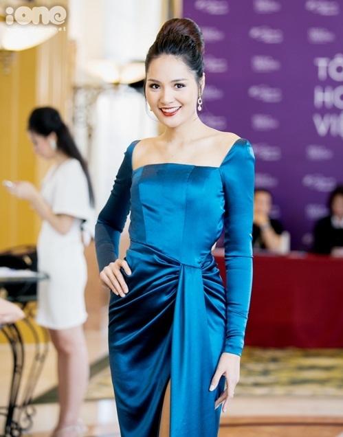 Hoa hậu Hương Giang chọn trang phục chất liệu vải lụa bóng. Cô búi tóc cổ điển.