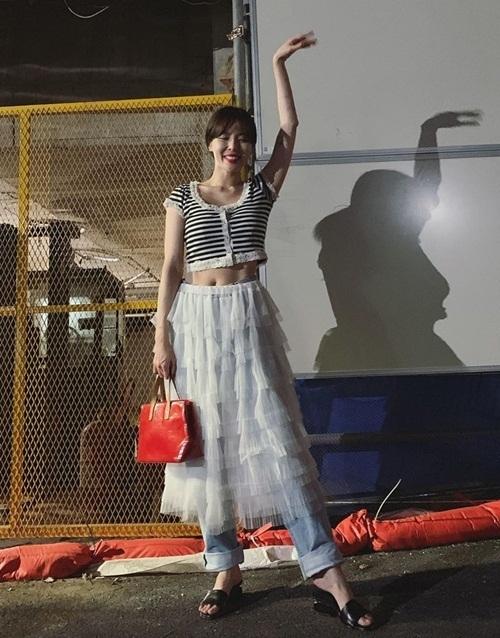 Hyuna khoe style độc đáo khi diện chân váy tầng bên ngoài quần jeans.