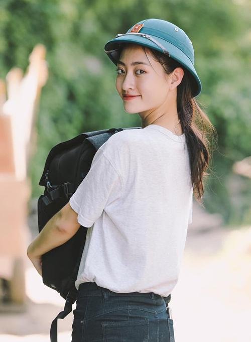 Hoa hậu Lương Thùy Linh diện áo phông trắng, đội mũ cối giản dị trong một chuyến đi từ thiện.