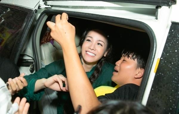 Nhiều fan theo chân Nhật Kim Anh ra tận xe để gửi gắm những món quà. Tại đây cô phải tiếp tục chiều fan pose hình chung.