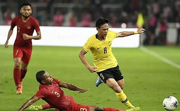 Cầu thủ Malaysia (áo vàng) trong trận gặp Indonesia. Ảnh: Antara News.