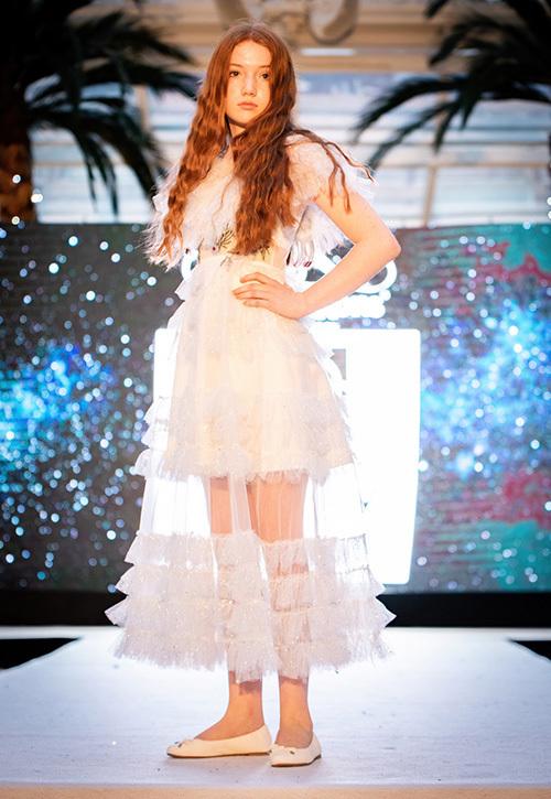 Gần 200 mẫu nhí - Việt kiều, Anh, Mỹ, Philippines - tham gia trình diễn. Các bé gái diện đầm xếp tầng duyên dáng, xinh đẹp như công chúa trên sân khấu. Các bé trai khoác lên người những mẫu suit hiện đại, gây ấn tượng bởi cách pose dáng tự nhiên, đáng yêu.