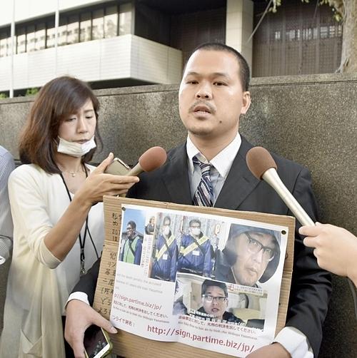 Bố bé Nhật Linh, anh Lê Anh Hào cầm biển kêu gọi chữ ký ủng hộ án tử hình với bị cáo Shibuya trước tòa án cấp cao Tokyo hôm 26/9. Ảnh: Kyodo