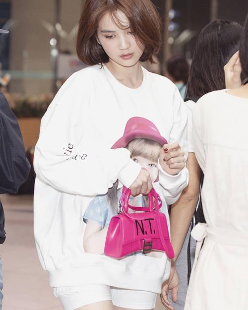 Ngọc Trinh vừa có mặt ở sân bay để lên đường đi công tác Hàn Quốc. Nữ hoàng nội y diện đồ kín đáo, nhí nhảnh với trang phục tông trắng hồng. Trên tay cô là chiếc túi Balenciaga Hourglass rực rỡ, được độ riêng bằng cách ghi chữ viết tắt tên của cô lên mặt túi.