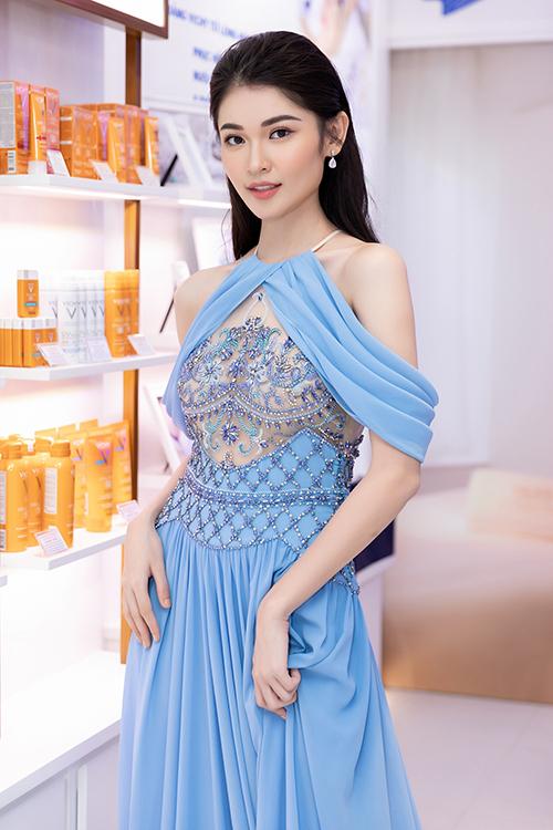 Á hậu Thùy Dung chọn váy dạ hội màu xanh của nhà thiết kế Lê Thanh Hòa đến dự khai trương một nhãn hàng. Bộ cánh hở vai kết hợp chi tiết đính đá bên trên lớp voan mỏng xuyên thấu giúp người đẹp khoe khéo nét gợi cảm.