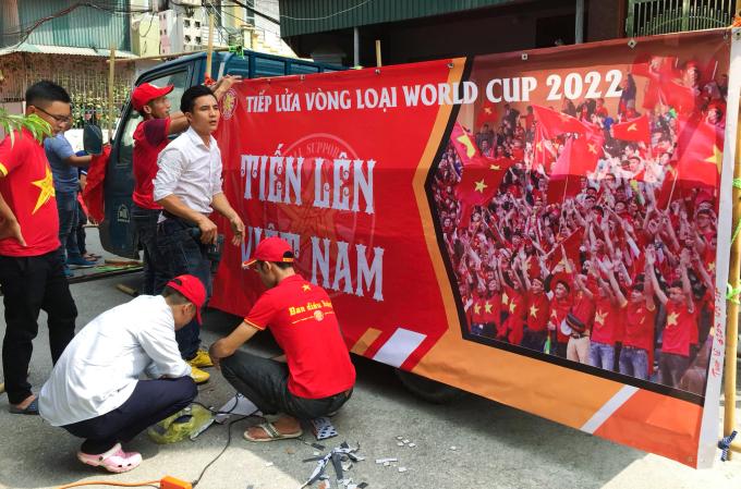 <p> Một nhóm người thuộc Hội CĐV bóng đá miền Bắc (VFS) mặc áo đỏ sao vàng, dán các khẩu hiệu lên xe để chuẩn bị diễu hành.</p>