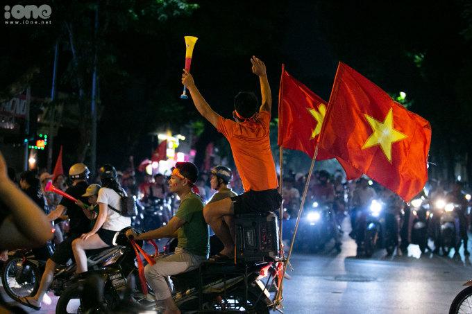 """<p> Cờ đỏ sao vàng tung bay khắp nhiều tuyến đường. Vừa đi, các CĐV này vừa hò hét, hô to """"Việt Nam vô địch"""".Đã khá lâu rồi không khí đường phố Thủ đô mới lại sôi động như thế này bởi người hâm mộ bóng đá.</p>"""